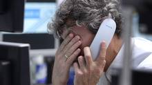 A trader makes a phone call at the stock market in Frankfurt, Germany, Thursday, Jan. 5, 2012. (Michael Probst/Michael Probst/AP)