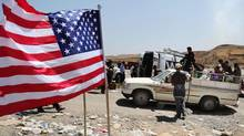 A U.S. flag waves at Feeshkhabour border point, northern Iraq, while displaced Iraqis from the Yazidi community cross the Syria-Iraq border on Feeshkhabour bridge over the Tigris River. (KHALID MOHAMMED/ASSOCIATED PRESS)