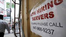 Pedestrians and shoppers walk past a 'Now Hiring' sign in Toronto in this file photo. (Deborah Baic/The Globe and Mail)