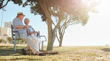 Retired couple sitting on a bench. (jacoblund/istockphoto)