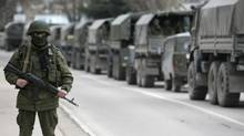 An armed serviceman stands near Russian army vehicles outside a Ukrainian border guard post in the Crimean town of Balaclava March 1, 2014. Ukraine accused Russia on Saturday of sending thousands of extra troops to Crimea and placed its military in the area on high alert as the Black Sea peninsula appeared to slip beyond Kiev's control. (Reuters)