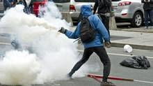 A demonstrator throws tear gas canister back towards the police line during a student demonstration outside the Montreal Convention Centre against hikes to university and college tuition fees on April 20, 2012 in Montreal. (Paul Chiasson / The Canadian Press)