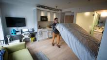 Samuel Baron, 29, lifts his murphy bed out of the way in the micro-loft where he lives at the renovated Burns Block on West Hastings Street, in Vancouver on Thursday. March 19, 2015. DARRYL DYCK FOR THE GLOBE AND MAIL (DARRYL DYCK/THE GLOBE AND MAIL)