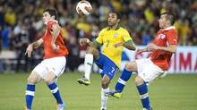 Brazil's Robinho (centre) pulls the ball down between Chile's Eugenio Mena (left) and Gary Medel during second half action of their international friendly match in Toronto on Tuesday November 19, 2013. (Chris Young/THE CANADIAN PRESS)