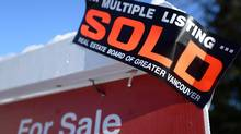 A real estate sold sign is shown outside a house in Vancouver in this file photo. (Jonathan Hayward/THE CANADIAN PRESS)