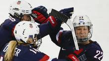 In this Feb. 17, 2014, file photo, Kacey Bellamy of the United States (right) is congratulated by teammates after scoring a goal against Sweden during the first period of the 2014 Winter Olympics women's semifinal in Sochi, Russia. (Julio Cortez/AP)