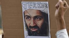 A member of the All India Anti-Terrorist Front gestures in front of a portrait of al-Qaeda leader Osama bin Laden during a pro-U.S. rally as the group celebrates bin Laden's killing, in Noida in the northern Indian state of Uttar Pradesh May 5, 2011. (PARIVARTAN SHARMA/REUTERS)