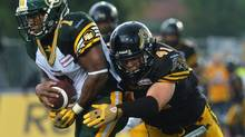 Edmonton Eskimos running back Hugh Charles, left, is tackled by Hamilton Tiger-Cats defensive back Erik Harris during fourth quarter CFL action in Guelph, Ont., Sunday, July 7, 2013. (Aaron Lynett/THE CANADIAN PRESS)