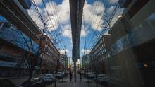 A westward view of King Street East is reflected in a storefront. (Tim Fraser for The Globe and Mail)