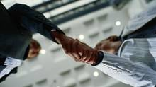 Businesspeople shaking hands, low angle view (Stockbyte/Getty Images)