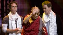 """His Holiness the Dalai Lama waves to youth attending """"We Day"""" as Craig and Marc Kielburger look on in Vancouver, Tuesday, Sept. 29, 2009. Dubbed ?The Day We Change The World,? the youth empowerment event calls on students to combat both local and global challenges. (Jonathan Hayward/The Canadian Press)"""