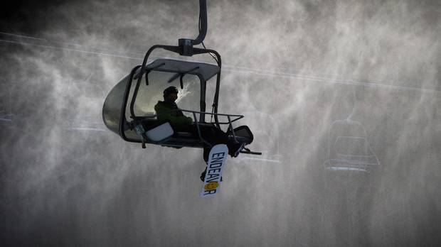 A snowboarder rides the Wizard Express chairlift down Blackcomb Mountain as snow from a snowgun hangs in the air in Whistler, B.C.