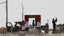 Egyptian soldiers are seen near the Kerem Shalom crossing, a zone where the Israeli, Egyptian and Gaza borders intersect and where an Egyptian military vehicle that was seized by Islamist gunmen tried to storm the border into Israel on Sunday, August 8, 2012. (AMIR COHEN/REUTERS)