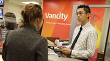 Vancity teller Tim Lu helps a client at the company's head office in Vancouver, B.C. (Lyle Stafford For The Globe and Mail)