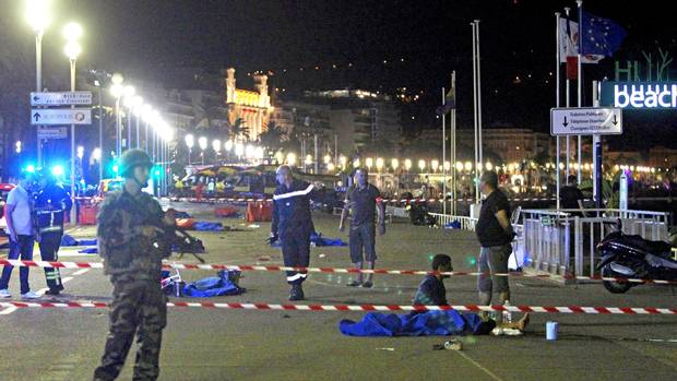 Soldiers, police officers and firefighters walk near dead bodies covered with a blue sheets on the Promenade des Anglais seafront in the French Riviera town of Nice on July 15, 2016, after a truck drove into a crowd watching a fireworks display.