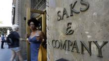 Shoppers use a Fifth Avenue entrance to Saks, in New York, Monday, July 29, 2013. The luxury retailer's Off 5th discount line will be getting a push as the company expands into Canada. (Richard Drew/AP)