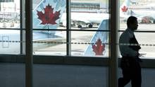 A person walks by Air Canada planes at Toronto Pearson Airport in this file photo. (Michelle Siu/THE CANADIAN PRESS)