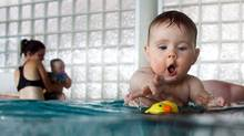 A toddler reaches for a rubber duck during a swimming class for babies at Lane Cove pool in Sydney, Australia.
