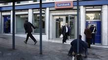 A beggar sits outside a Eurobank branch in Athens Dec. 10, 2012. Greek banks this week sold back all or most of their sovereign debt holdings at prices well below nominal value to meet IMF targets. (Yorgos Karahalis/Reuters)