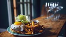 The burger topped with a fried egg and a side of chips are seen at the Farmhouse Tavern in Toronto on January 23, 2013. (JENNIFER ROBERTS FOR THE GLOBE AND MAIL)