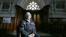 Gilbert Pelletier sits in L'Église de L'Isle-Verte, awaiting word on the fate of his aunt. (Christinne Muschi for The Globe and Mail)