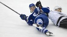Leafs Peter Holland(24) takes a holding penalty against LA Kings Slava Voynov(26) during the first period of the NHL game between the Toronto Maple Leafs and the Los Angeles Kings at the ACC in Toronto on Dec. 11, 2013. (Peter Power/The Globe and Mail)