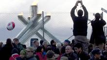 Visitors stand on cement barriers behind a fence to take souvenir photos of the Olympic cauldron in Vancouver. (Paul Chiasson/The Canadian Press)