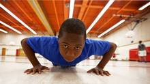 Tad Pfupa, 13, demonstrates exercises he does in the physical education ACE program at Camilla Road Senior Public School in Mississauga on May 16, 2012. Before he started the program, he could only do 30 pushups and now he can do 70 pushups. (JENNIFER ROBERTS/Jennifer Roberts for The Globe and Mail)