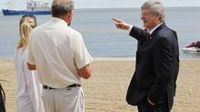 Prime Minister Stephen Harper points to a research ship as he talks to Lake Winnipeg researcher Dr. Al Kristofferson (L) on Gimli Beach Thursday, August 2, 2012. Harper announced funding for second phase clean up of Lake Winnipeg at a press conference. (JOHN WOODS/THE CANADIAN PRESS)
