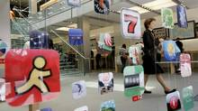 A woman walks past icons for Apple apps at the company's retail store in San Francisco, California in this April 22, 2009 file photo. Canada's Privacy Commissioner has joined 22 of his counterparts within Canada and around the world to issue an open letter asking tech giants such as Google Inc. and Apple Inc. to better control user privacy in mobile applications. (ROBERT GALBRAITH/REUTERS)