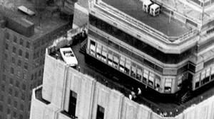 A 1966 Mustang convertible is perched on a corner of the 86th floor parapet of the Empire State Building