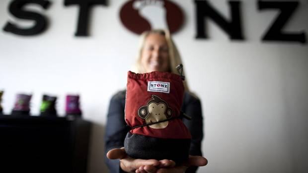 Lisa Will, founder and chief executive officer of Stonz Wear Inc., an infants' and children's outerwear company, holds a bootie at the company's warehouse in Vancouver. (Rafal Gerszak For The Globe and Mail)