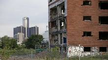 One of the last two remaining vacant 15-story towers at Brewster-Douglass housing complex is seen during demolition with the General Motors World Headquarters in the skyline just north of downtown Detroit, Michigan June 26, 2014. The Brewster-Douglas complex, vacant since 2008, are remembered as the place where Motown Stars such as Diana Ross grew up. (Rebecca Cook for the Globe and Mail) (REBECCA COOK For The Globe and Mail)