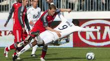 Vancouver Whitecaps Atiba Harris is hauled down by Toronto FC defender Ty Harden during the second half of their season-opening MLS game. (BEN NELMS/Reuters)
