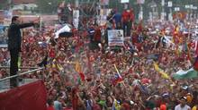 Venezuelan President Hugo Chavez greets supporters in the rain during his closing campaign rally in Caracas on Thursday. (JORGE SILVA/REUTERS)