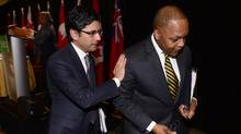 Ontario Attorney-General Yasir Naqvi pats Justice Michael Tulloch on the arm after he released his recommendations on how to enhance oversight of policing in the province at a news conference in Toronto last week. (Frank Gunn/The Canadian Press)