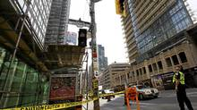 A police officer looks up where glass had fallen from a highrise in downtown Toronto at Bay and Grenville Streets injuring one person on Aug.15, 2011. (Michelle Siu/Globe and Mail/Michelle Siu/Globe and Mail)