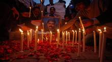 Men light candles during a candlelight vigil in commemoration of assassinated Pakistani Minister for Minorities Shahbaz Bhatti, in Lahore March 5, 2011. (© Mohsin Raza / Reuters/REUTERS)