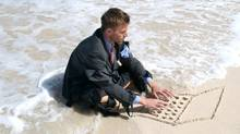 Castaway Businessman Types on Sand Computer Wave (PeskyMonkey/Getty Images/Vetta)