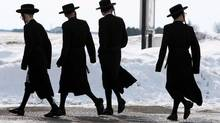 Members of the Lev Tahor ultra-Orthodox Jewish sect walk down a street in Chatham, Ont., March 5, 2014. (Dave Chidley/The Canadian Press)