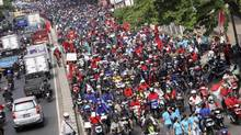Workers ride their motorcycles along a street during a demonstration over labour issues in an industrial area of Tangerang, on the outskirts of Jakarta October 3, 2012. More than 30,000 workers in several of Indonesia's provinces staged a strike demanding improvements in their contracts and better wages, a police officer said on Wednesday. (STRINGER/INDONESIA/REUTERS)