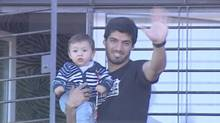 Uruguayan striker Luis Suarez carries his son Benjamin as he waves to supporters from the balcony of his house in the small coastal town of Solymar, in the outskirts of Montevideo in this June 27 still image taken from footage provided by Television Nacional Uruguay via Reuters TV. (REUTERS TV/REUTERS)