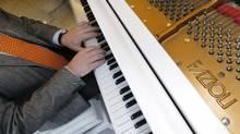 Paolo Fazioli, Italian piano magnate, plays a Fazioli piano in the lobby of the Fairmont Pacific Rim hotel in Vancouver in January. (The Globe and Mail)