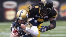 Winnipeg Blue Bombers starting quarterback Buck Pierce is tackled by Hamilton Tiger Cats Renauld Williams (Chris Young/The Canadian Press)