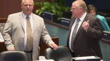 Toronto Mayor Rob Ford (right) talks to his brother Councillor Doug Ford as they attend the last council meeting of this term at City Hall on Monday August 25, 2014. (Chris Young For The Globe and Mail)