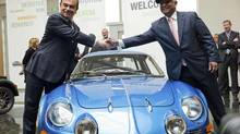 Renault's Carlos Ghosn, left, and Caterham Group chairman Tony Fernandes shake hands over an Alpine sports car in Boulogne-Billancourt, near Paris, on Monday. The two auto makers announced a joint venture to develop sports cars. (JULIEN MUGUET/REUTERS)