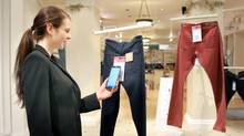In this undated photo provided by Hointer, a woman demonstrates the Seattle store's shopping technology. Hointer displays clothing not in piles or on racks but as one piece hanging at a time, like a gallery. Shoppers just touch their smartphones to a coded tag on the item and then select a colour and size via their phone. Technology in the store keeps track of the items, and by the time a shopper is ready to try them on, they're already at the dressing room. (HOINTER/THE ASSOCIATED PRESS)
