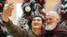 """Jack Wang takes a selfie with Paul Mason the resident, """"Fashion Santa,"""" at Yorkdale mall in Toronto during Black Friday sales on Nov. 27, 2015. (Jennifer Roberts/The Globe and Mail)"""