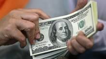 A woman counts her U.S. dollar bills. (BEAWIHARTA/REUTERS)