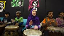 Marwa Hibak, 11, plays music during a celebration of life to the late former president of South Africa Nelson Mandela at the Nelson Mandela Park Public School in Toronto, Friday December 6, 2013. (Mark Blinch/THE CANADIAN PRESS)